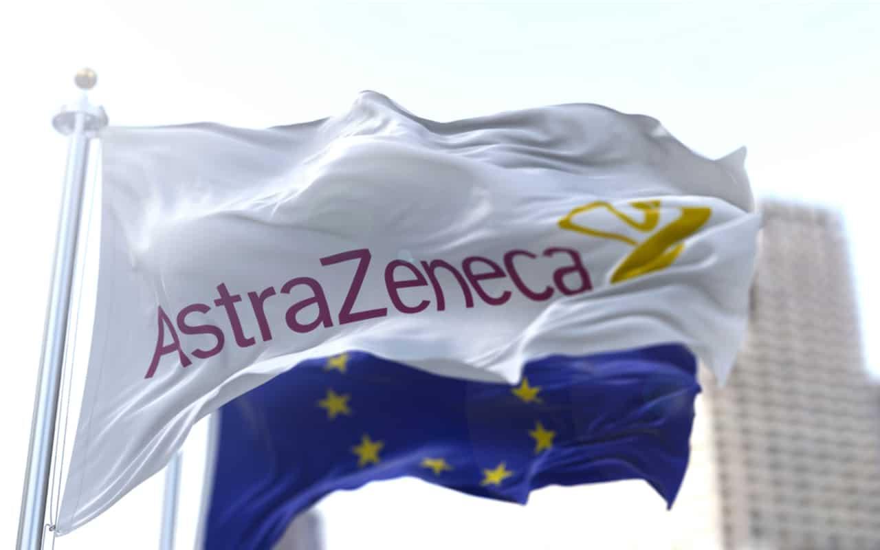 Bandiera bianca con il logo Astrazeneca che sventola con la bandiera europea sullo sfondo.